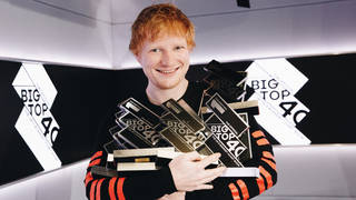 Ed Sheeran poses with his 14 Official Big Top 40 Number 1 trophies