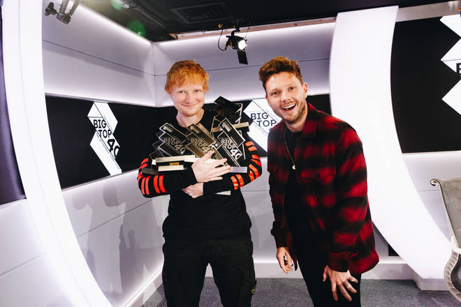Ed Sheeran holding his Number 1 trophies alongside Will Manning